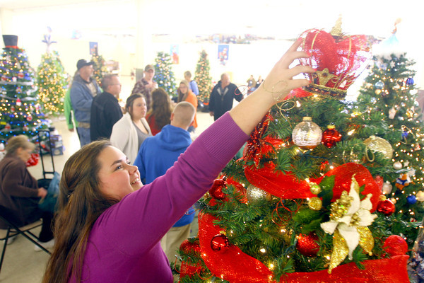 """11-3-13  --  We Care Trim-a-Tree in the old Phar Mor store at the Kokomo Town Center(across from the movie theater) decorating on Sunday for the auction that will take place Sunday Nov. 17. Chaslyn Sheppard works on positioning the topper on the """"Queen for a Cause"""" tree that her and Gabrielle Bunn where decorating.<br />   KT photo 