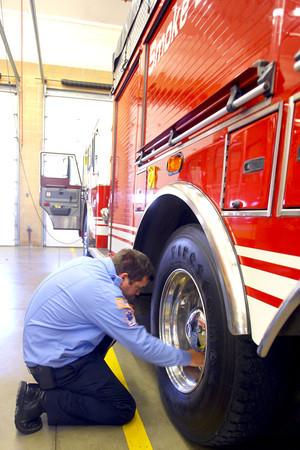 11-14-13  --  Peru Fire Department --  Firefighter Greg Hunt checking air pressure on the ladder truck tires.<br />   KT photo | Tim Bath
