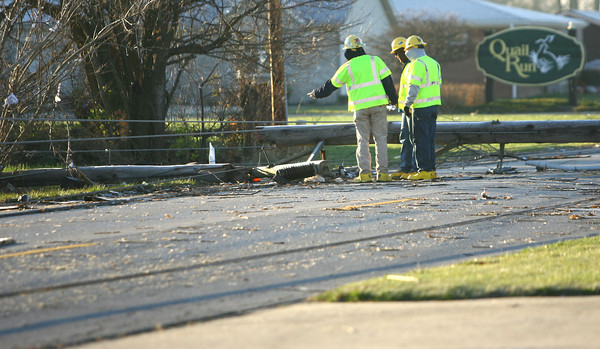 The tornado took down the high voltage wires and poles on Guyer Road on Sunday. Pike Electric workers out of Cincinnati remove and replace the lines on Tuesday.<br />   KT photo   Tim Bath