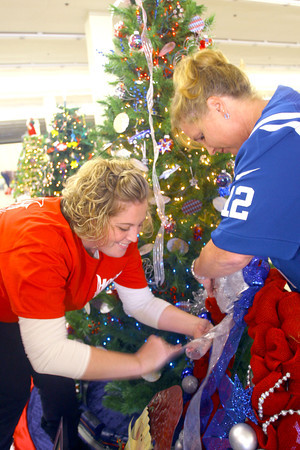11-3-13  --  We Care Trim-a-Tree in the old Phar Mor store at the Kokomo Town Center(across from the movie theater) decorating on Sunday for the auction that will take place Sunday Nov. 17. Kristen Challis and Julie Brubaker put the finishing touches on the Hog Runner's tree.<br />   KT photo | Tim Bath