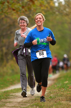 10-13-12<br /> Run the Shores<br /> Melissa Meck (foreground) and Laura Cook smile as they are cheered on during Run the Shores 5K.<br /> KT photo | Kelly Lafferty
