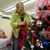 10-28-12<br /> We Care Trim-A-Tree decorating<br /> Janet Fallon spots Lori Thomas on the stepladder before Thomas reaches up to add ribbon on the WWKI tree. The two were laughing saying it reminded them of when they used to be cheerleaders.<br /> KT photo | Kelly Lafferty