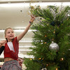 10-28-12<br /> We Care Trim-A-Tree decorating<br /> With the help of her dad Brian Hayes holding her up, 7-year-old Chase Hayes reaches to put the tree-topper on top of the Hayes Advisory Group on Sunday during the We Care tree decorating.<br /> KT photo | Kelly Lafferty