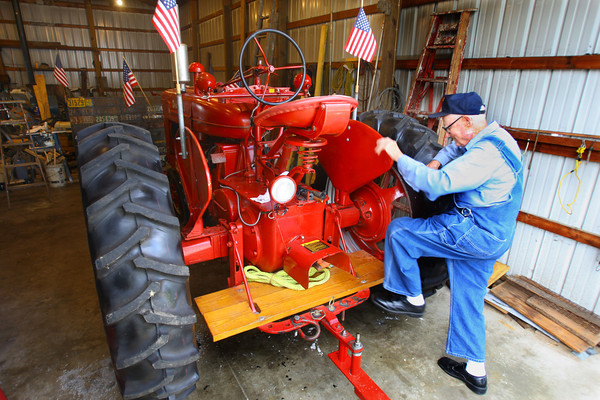 10-2-13  --   Meredith Kingery and his wife June have lived on north Wabash since 1947. Climbing onto the old Farmall tractor that he likes to take to all the downtown parades.<br />   KT photo | Tim Bath