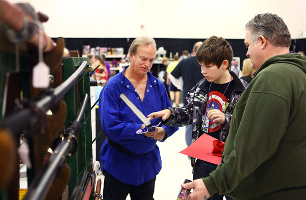 10-19-13<br /> Kokomo-Con<br /> Tim Hight lets Nathan Dolin touch the master sword from Zelda as Dave Dolin watches during Kokomo-Con at the event center on Saturday.<br /> KT photo | Kelly Lafferty