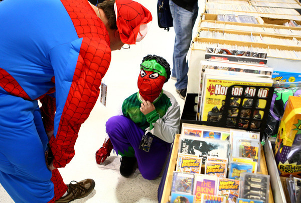 10-19-13<br /> Kokomo-Con<br /> Noah Thompson looks up at Jeremey Thompson after looking through items for sale at Kokomo-Con on Saturday.<br /> KT photo | Kelly Lafferty