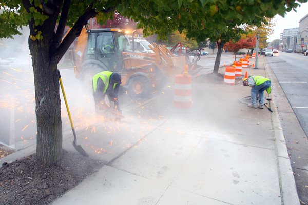 10-30-13  --  City of Kokomo workers remove the concrete around trees in the 100 block of north Union Street to remove the trees as part of the parking garage and YMCA building projects.<br />   KT photo | Tim Bath