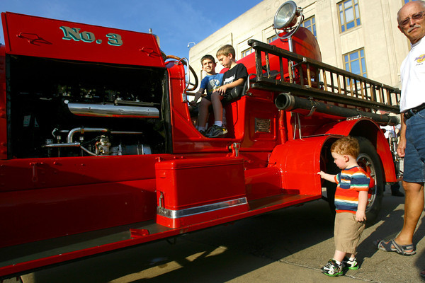 9-6-13  --  Hayden Myers, 9, and Jacob Myers, 7, sit in the seat of a 1915 Model K2 Ahrens Fox that the City of Kokomo used from 1915 till 1953. Grayson Humphrey, 2, waits his turn to sit in the seat again. This was during First Friday Downtown on Sept. 6.<br />    KT photo | Tim Bath