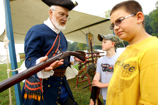 """9-20-13  --  Dan Segal from Detroit operator of """"The French Trade Gun,"""" showing off his collection of guns and riffles at Koh-Koh-Mah & Foster Encampment with 4th graders, about 1700 of them, visiting. Alex Fox, 9, and Colton Edwards, 10 listen to how the weapons have changed over the years.<br />    KT photo   Tim Bath"""