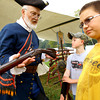 "9-20-13  --  Dan Segal from Detroit operator of ""The French Trade Gun,"" showing off his collection of guns and riffles at Koh-Koh-Mah & Foster Encampment with 4th graders, about 1700 of them, visiting. Alex Fox, 9, and Colton Edwards, 10 listen to how the weapons have changed over the years.<br />    KT photo 