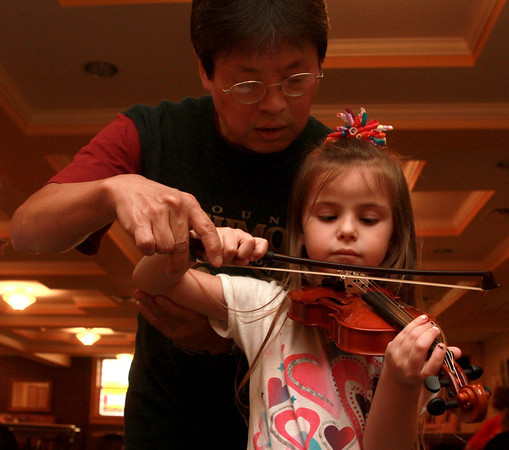 9-12-12<br /> Youth program strings instructional class<br /> Instructor Moo Il Rhee helps 5-year-old Aviana Haigh to pull the bow across her violin strings during the youth program strings instructional class on Wednesday.<br /> KT photo | Kelly Lafferty