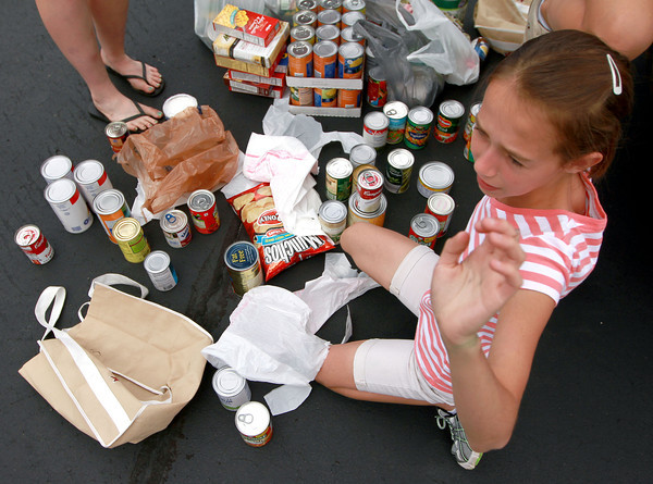 """9-9-12<br /> Canned Food Drive<br /> Rebecca Collins, 12, of Bible Baptist Church waves down someone from her group as she sorts through canned goods in the parking lot of Bible Baptist for the """"Yes, We Can!"""" food drive on Sunday.<br /> KT photo 
