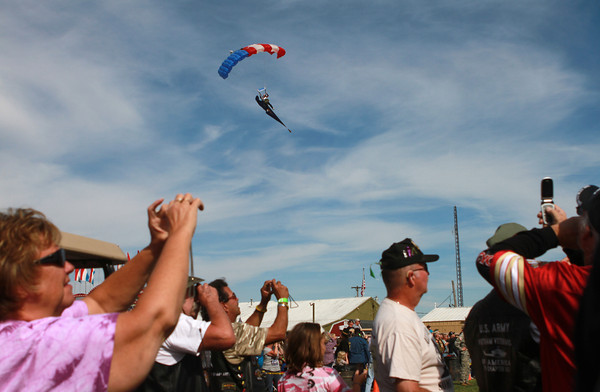 9-15-12 <br /> Vietnam Vet Reunion Saturday<br /> People hold up their cameras and cellphones to take pictures of the parachuters who landed at the Vietnam veteran reunion campgrounds on Saturday.<br /> KT photo | Kelly Lafferty