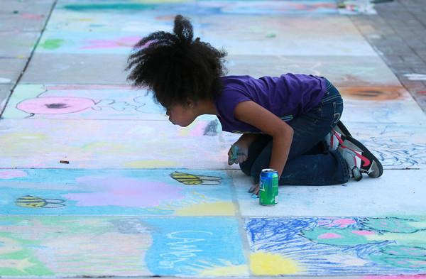 9-28-12<br /> Oktoberfest<br /> Brooklyn McKelvin, 10, blows chalk dust off her creation during Chalk the Block at Oktoberfest on Friday.<br /> KT photo | Kelly Lafferty