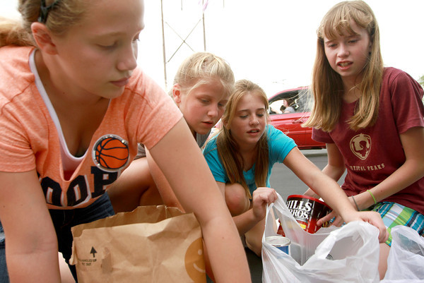 9-9-12<br /> Canned Food Drive<br /> From left, Jaid Cassity, 12, Lexie Howell, 11, Katilynn Burke, 11, and Paige Bennett, 12, of Fairfield Church separate and search for certain canned foods to barter with other groups so they can collect the most cans of their mega-food.<br /> KT photo | Kelly Lafferty