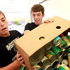 "9-9-12<br /> Canned Food Drive<br /> Tyler McKay, 15, left, and Josiah Brown, 17, work together to dump a box of canned food into a large box in one of the trucks at the ""Yes, We Can!"" food drive on Sunday at Bible Baptist Church.<br /> KT photo 
