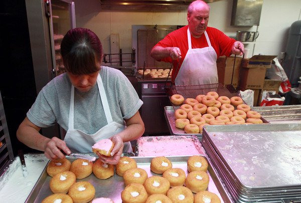9-22-12<br /> Dan's Donuts at 1 AM<br /> Patty Vannatter ices donuts while Danny Haworth takes donuts out of the deep fryer at Dan's Donuts early Saturday morning.<br /> KT photo | Kelly Lafferty