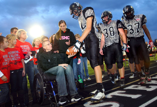 9-28-12 <br /> At the Western HS vs. Eastern HS football game, between the first and second quarter Zach Nelson is honored with the game ball by the Western team. Ronnie Smith handed him the ball. Money was collected throughout the stands to help the Nelson family. A monument was also dedicted before the game to honor veterans inspired by Nelsons bravery. Nelson was paralized July 5 of this year while serving in Afghanistan.<br /> KT photo | Tim Bath