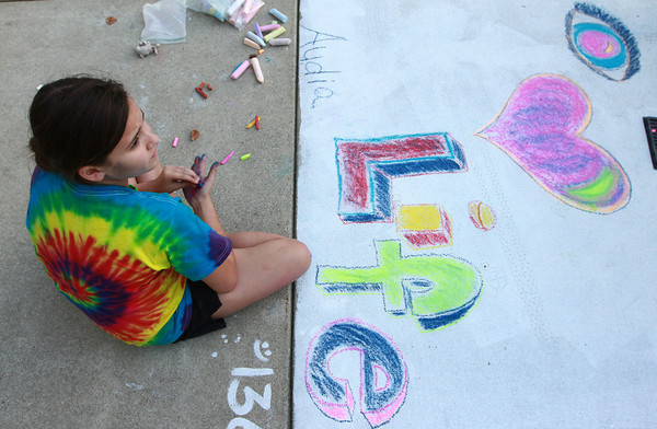 9-28-12<br /> Oktoberfest<br /> Audia Anders, 11, pauses as she completes her art creation during Chalk the Block at Oktoberfest on Friday.<br /> KT photo | Kelly Lafferty
