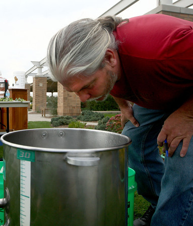9-20-12<br /> Homebrewing at the library<br /> Dave Johnson smells the batch of brewing beer after hops had been added to it during the demonstration of homebrewing at the library.<br /> KT photo   Kelly Lafferty