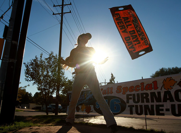9-11-12<br /> Little Caesars Rebecca Vann<br /> Shakerboarder Rebecca Vann, spins her Little Caesars sign at the intersection of Markland and Washington. Vann taught herself how to shakerboard.<br /> KT photo   Kelly Lafferty