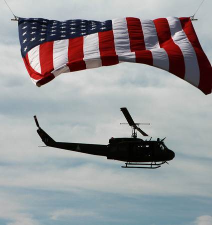 9-15-12 <br /> Vietnam Vet Reunion Saturday<br /> A helicopter flies underneath the American flag and around the Vietnam veteran reunion campsites on Saturday.<br /> KT photo | Kelly Lafferty