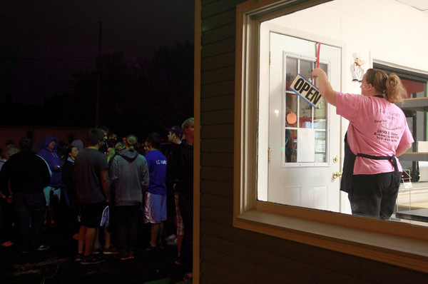 """9-22-12<br /> Dan's Donuts at 1 AM<br /> Kathy Harris flips the sign from """"Closed"""" to """"Open"""" at 1 a.m. at Dan's Donuts as a line waits outside to go inside.<br /> KT photo 