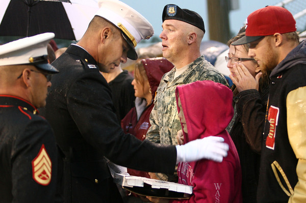 9-21-12 <br /> Sgt. Bradley Atwell's Family receiving a purple heart at the Taylor Football game by the Marine Corp. on Friday. Bradley was killed in Afghanistan last week. Bradley's sister Lauren Atwell receives the purple heart from Capt. Marcus Trouerbach with Bradley's step mother Kimberlee behind her. Josh Hale stands saluting with the family.<br /> KT photo | Tim Bath