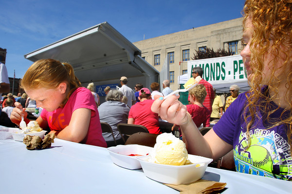 6-5-14   --- Jo Trine, 10 and sister Kaylin Trine, 15, enjoying their strawberry shortcake at the Strawberry Festival downtown. --<br />   Tim Bath   Kokomo Tribune