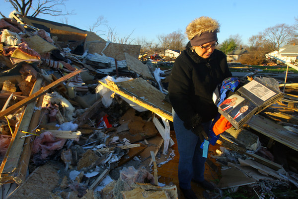 Phyllis Rawlins goes through items in her house that was destroyed on Ricketts. She found a photo album that was open to the page with her late husband. He build the house 8 years ago for there retirement and passed away last year.<br />   KT photo | Tim Bath