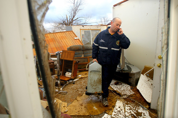 Todd Woolf, a Grissom Firefighter who lives in the Cedar Crest neighborhood sift through debree looking for medication and oxygen supplies. Colleen Carney lived in the house on Saratoga and survived the tornado by sitting in a car in the garage.<br />   KT photo   Tim Bath