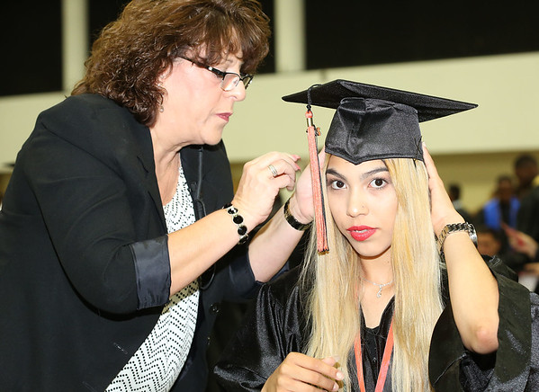 051718 - WEST PALM BEACH - John I. Leonard High School graduation at The South Florida Fairgrounds on Thursday, May 17, 2018. Pictured is Kayla Acosta having her hat adjusted by Mary Ann Moore, Algebra teacher at John I. Leonard. Photo by Tim Stepien.