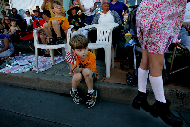 November 19, 2006_ZACHARY LANG, 5, left, and his brother, GABRIEL LANG, 5, of San Diego, center, holds a flag, while an excited VALORIE GLASSER, 8, of El Cajon, right, jumps at the start of the 60th Annual Mother Goose Parade in El Cajon.