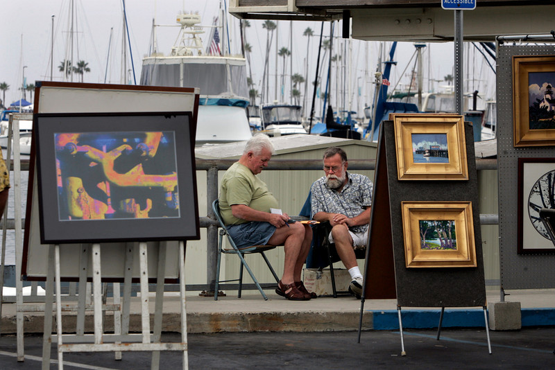 Chick Hinkle of Huntington Beach, left, shows photos to artist Scott Kuhnly of Escondido, right, near Kuhnly's booth at Oceanside Harbor Days. The two were looking at photos of Hinkle's retirement home that was flooded in Biloxi, Mississippi, which held 30-50 paintings that he had purchased from Kuhnly.--Laura Embry/Union-Tribune