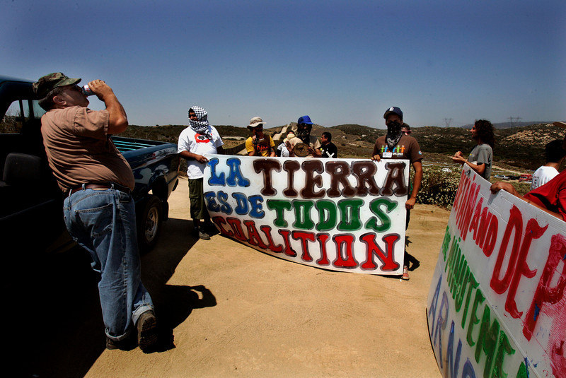 California Minutemen volunteer Jim Fowler of Santee,  sips a soda while protestors confront him with signs and yell for him to leave the dirt road that parallels the border fence near Campo.--Laura Embry/Union-Tribune