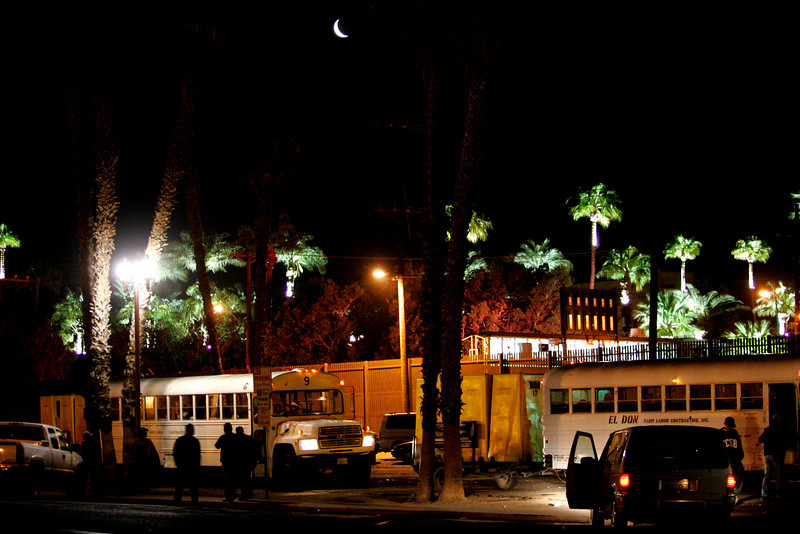 March 15, 2007_Calexico, CA_A new moon shines over white buses that line a parking lot in Calexico, California at 5:00 a.m., on the United States side of the US/Mexico border crossing from Mexicali, Baja California. Labor contractors wait for the workers, who fill their buses in search of day work in the fields of Imperial Valley and Yuma, Arizona. Floodlights illuminate the border crossing between the United States and Mexico._Mandatory Credit photo by Laura Embry/San Diego Union-Tribune/Zuma Press, copyright 2007 San Diego Union-Tribune