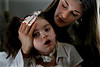 Joanna Endermann holds her daughter,  Gloria, 5, in her Escondido home. Gloria nearly drowned in 2004 and has damage to her brain.--Laura Embry/Union-Tribune