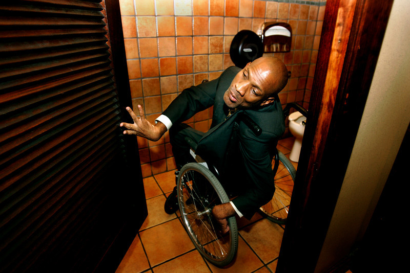 July 25, 2006_La Jolla, CA _THEODORE PINNOCK, who has cerebral palsy and must use a wheelchair, shows the bathroom at an accessible restaurant called Cozymel's Mexican Grill in La Jolla. PINNOCK has made a career of suing or threatening to sue thousands of businesses alleging violations of the Americans with Disabilities Act. Tomorrow ( July 26) is the 16th anniversary of ADA being signed into law.