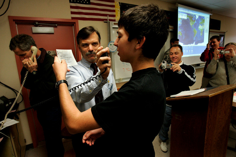 Mt. Carmel High School Amateur Radio Club member Marc Russell, 15, center,  practices his question for Commander Bill McArthur, an astronaut on the International Space Station Expedition 12, while his club advisor and Mt. Carmel science teacher John Earnest holds a microphone, just moments before the space station reached an orbit over California and communicated with the ham radio club in Earnest's classroom at the high school in Rancho Penasquitos. At left; is Randy Standke, an engineer for Qualcomm, who volunteered to help the club and at right, is parent Randy Yerrick, who videotaped the 10-minute event.--Laura Embry/Union-Tribune
