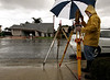 A surveyor with Right of Way Engineering in Oceanside uses an umbrella to cover his gear as he moves to the back of the house at 1909 Arroyo Avenue in Oceanside after taking a measurement from across the street during a sudden downpour. The homes on Arroyo Avenue are checked twice a day, since they are sliding downhill onto homes on Comanche Street below. (NOTE: THIS GUY DOES NOT WANT TO BE IDENTIFIED)--Laura Embry/Union-Tribune