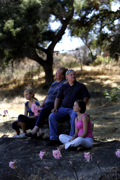 The Bellante family, from left; Lindi, 13, Lori, Lonnie and Melanie, 15,  enjoys a cool breeze as they sit on a rock overlooking the spot where their home burned near Barona Indian Reservation in the Cedar fire and where their new house will be built by Habitat For Humanity. The group is eager to start construction after getting permission from the tribe to access their land and were discussing where the front porch should be located .--Laura Embry/Union-Tribune