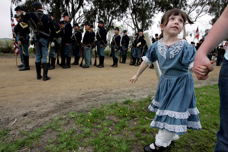 Jordan Owens, 6, of Apple Valley, California, right, stands with her cousin Ashley Link of Capo Beach, California, on the grounds of the Antique Gas & Steam Engine Museum, in Vista, as the Union troops mass in preparation for a Civil War reenactment there.