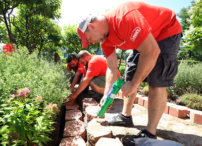 Lowe's Home Improvement Service Manager Dan Joy (right) applies landscaping adhesive to decorative bricks as Customer Service Associates Stephen Peebles (left) and Nick Peebles (center) put the blocks in place during the Lowe's Special Heroes volunteer project at the Samuel F. Vilas Home in Plattsburgh. More than 20 Lowe's employees spent the day revamping the landscape at the home by adding mulch and decorative bricks. Lowe's also donated a new washer, air conditioners, four park benches and two patio sets for residents to enjoy. Volunteers also stained the porch, deck and handicap ramp with stain donated by Sherwin-Williams.The volunteer project is part of the Lowe's Special Heroes program, a nonprofit community project where Lowe's employees are encouraged to volunteer to help make a difference in their community. KAYLA BREEN/ STAFF PHOTO