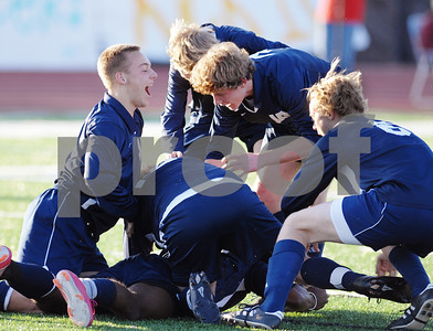 Forward A.J. Arnold (bottom) is swarmed by his teammates after scoring a first-half goal during Saturday's MAIS divisional semifinal game against Jackson Prep.