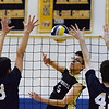 CARL RUSSO/staff photo. Haverhill's Patrick Gosselin spikes the ball as Andover's Timothy Liu, left, and Steven Crowley defend. Andover against Haverhill in volleyball action Monday afternoon. 4/30/2018