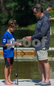 AMANDA SABGA/Staff photo   Vincent Giaimo, 9, gets help unhooking his fish from Jim Lagacy, Angler Education coordinator at  Mass. Wildlife, who hosts as fishing workshop at Pomps Pond in Andover.   8/20/18