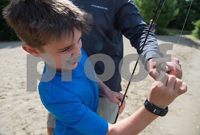 AMANDA SABGA/Staff photo   Zach Enners, 9, unhooks his bait from a fish he caught as Mass. Wildlife hosts as fishing workshop at Pomps Pond in Andover.   8/20/18