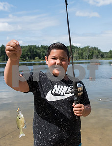 AMANDA SABGA/Staff photo   Alex Tran, 10, poses with his fish as Mass. Wildlife hosts as fishing workshop at Pomps Pond in Andover.   8/20/18