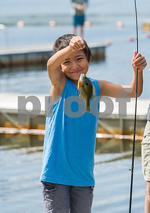 AMANDA SABGA/Staff photo   Gabe Shneer, 7, poses with his fish as Mass. Wildlife hosts as fishing workshop at Pomps Pond in Andover.   8/20/18