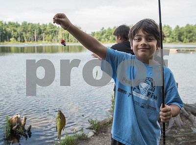 AMANDA SABGA/Staff photo   Mir Durrani, 8, poses with his fish as Mass. Wildlife hosts as fishing workshop at Pomps Pond in Andover.   8/20/18